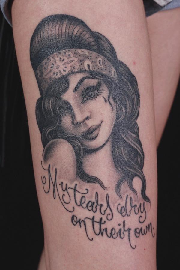 sam-yamini-dedication-tattoo-black-and-grey-girl-script-amy-winehouse-thigh